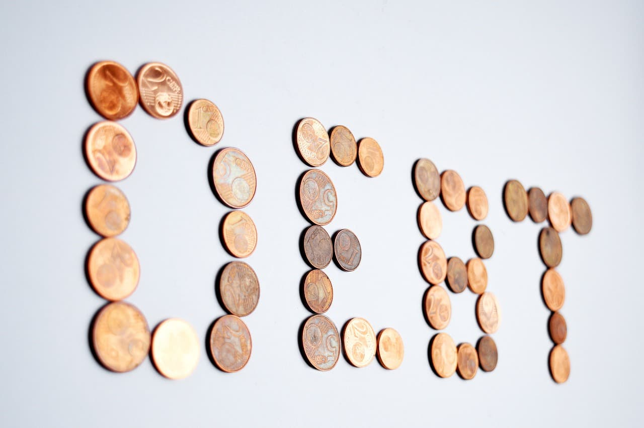 the word debt spelled out in pennies