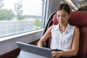 woman sitting on a train typing on her laptop