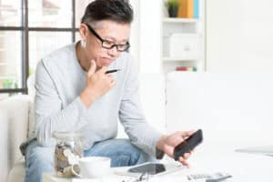 Asian man doing analysis on his business budget, looking on tablet pc and smart phone.