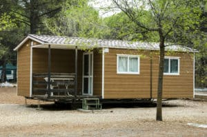 a brown mobile home in the woods