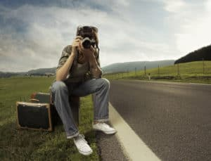 a woman sitting on a suitcase by the side of the road taking a picture