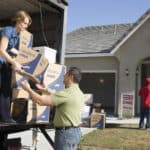 couple-unloading-moving-boxes-from-truck-into-new-house