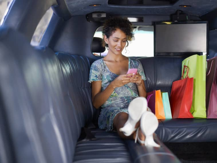 woman sitting in limousine with shopping bags and typing on mobile phone.