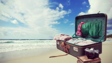 Open suitcase with old books and camera with seaside and blue sky on background.