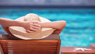 Luxury female tanning on the beach, wearing big stylish hat, enjoying beautiful seascape