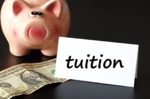 education tuition concept with piggy bank on black background