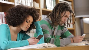 Two college students texting text messages at library
