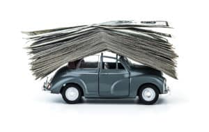 Side view on small decorative car model carries on itself a lot of cash isolated on white background