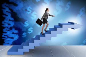 Businesswoman climbing career ladder in business concept