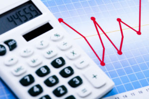 calculator with a chart behind it -What Do Landlords Look for in Your Bank Statement