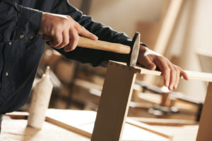 Carpenter hammering a piece of furniture for assembly. -What Are Some Alternatives to Renting an Apartment or Buying a House