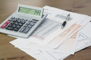 Calculator and Pen on Bank statement and credit card statements on a Wooden table -What is a Good Credit Score to Get an Apartment Without a Cosigner