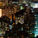 Landscape of city apartments illuminated in the night.