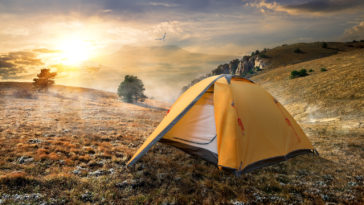 Tourist tent in autumn mountains at sunrise