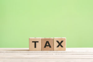 Tax sign made of wood on a green background