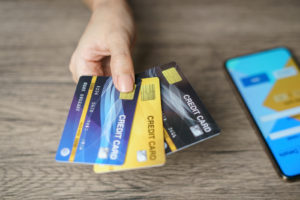 Woman hand showing her many credit card with smart phone -How Much of Your Salary Should You Spend on Rent