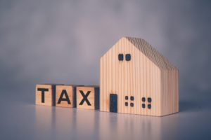 Wooden block cube with TAX word and home model -What Happens to a Tenant if the Landlord Doesn't Pay the Property Tax