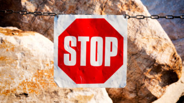 Metal stop sign on the chain with stones in background