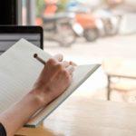 freelance writer sitting by a window
