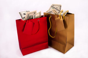 A gold and a red gift bag with dollars -Is 20 Million Dollars a Lot of Money