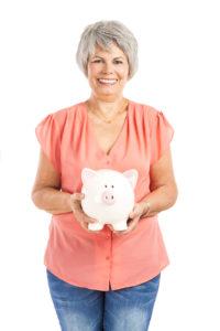 older woman holding piggy bank