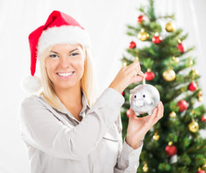 woman holding a piggy bank standing next to a christmas tree