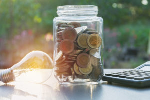 jar with coins and a light bulb next to it