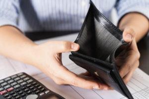 woman's hand open empty wallet looking for money