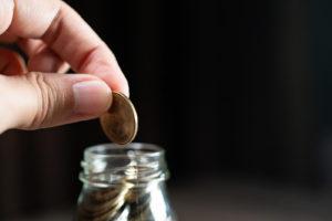 a hand putting a coin in a jar