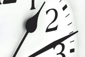 Detail of a clock. Pointer shows quarter past one