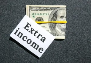 Dollars cash money and paper note with text written EXTRA INCOME
