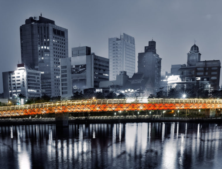 Cityscape of apartments with river and bridge in night.